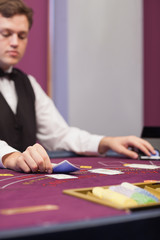 Dealer in a casino stacking cards