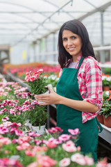 Worker holding a flower and smiling