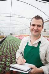Smiling man taking notes in greenhouse
