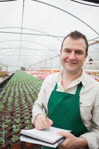 Smiling man taking notes in greenhouse