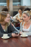 Student comforting upset friend with mobile phone
