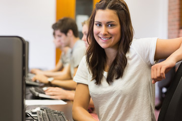 Student sitting at the computer room smiling