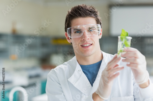 Student standing at the laboratory holding beaker with seedling