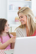 Daughter pointing at laptop with mother