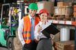 Two Confident Young Supervisors At Warehouse