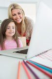 Mother standing behind daughter looking at laptop