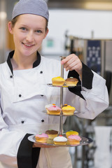 Smiling chef holding tiered cake tray