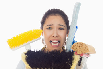 Very stressed woman with cleaning tools