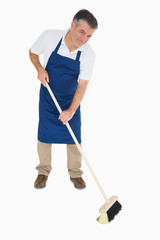 Happy man sweeping floor