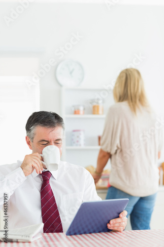 Man drinking coffee and using tablet pc