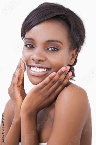Woman putting on moisturizer