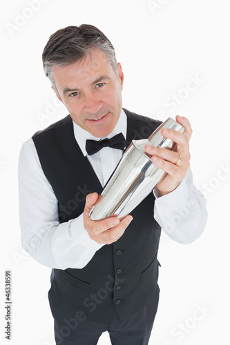 Waiter shaking drink in cocktail shaker