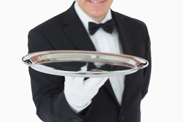 Smiling man holding a silver tray
