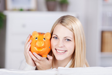 lächelnde junge frau mit sparschwein