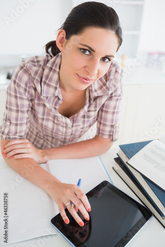 Woman using an ebook while looking at camera