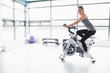 Happy woman riding an exercise bike