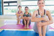 Smiling women sitting on yoga mats