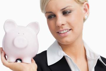 Cute businesswoman holding a piggy-bank