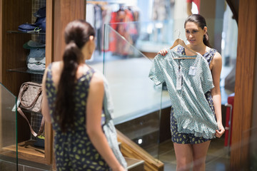 Woman is looking in the mirror while holding up clothes