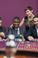 Three men and a woman at roulette table