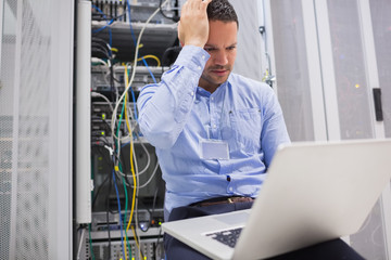 Man getting stressed with laptop over servers