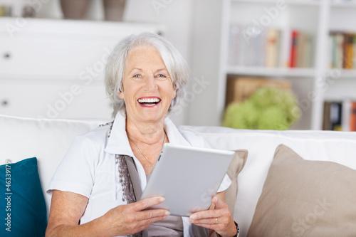 lachende ältere dame mit tablet-pc