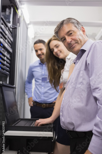 Three happy technicians checking servers with laptop