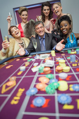 Women celebrating man's success at roulette