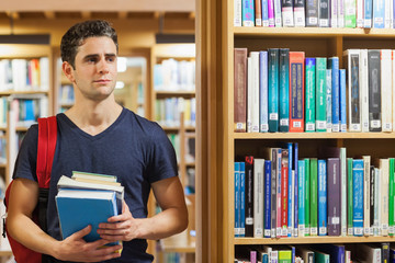 Student standing at the library holding pile of books