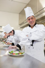 Happy chef with others preparing salads