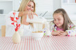 Woman pouring milk into a glass for daughter