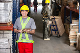 Mid Adult Foreman With Digital Tablet At Warehouse