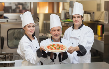 Three Chef's holding a pizza