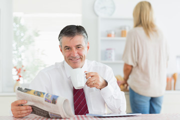 Man sitting at the kitchen table while holding a cup of coffee b