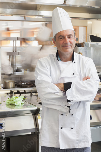 Chef leaning at counter in busy kitchen