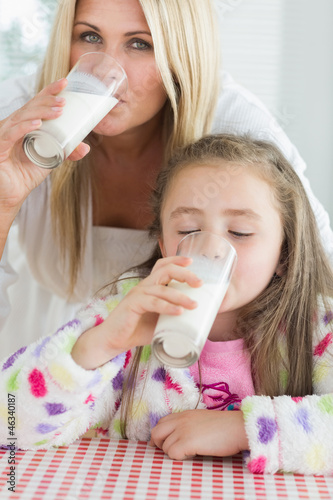 Mother and little girl drinking milk