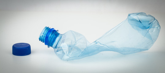 Empty plastic bottle crushed and blue cap