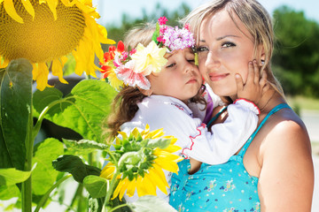 mother with her daughter, summer time with sunflowers