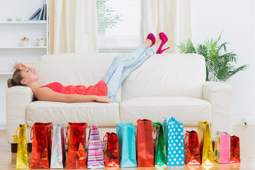 Woman lying on the sofa tired after shopping