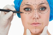 Plastic surgeon drawing on face