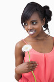 Girl standing holding a flower while smiling against white backg