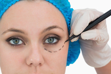 Plastic surgeon writing on the serious woman's face