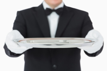 Waiter holding a silver tray with both hands