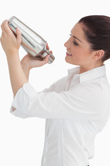 Woman using cocktail shaker while looking at it