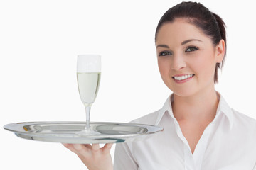 Woman carrying tray with glass of champagne