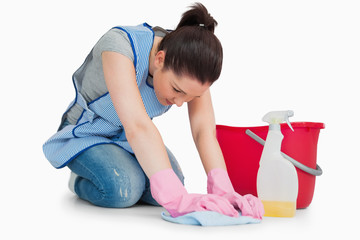 Serious cleaning woman wiping up the floor