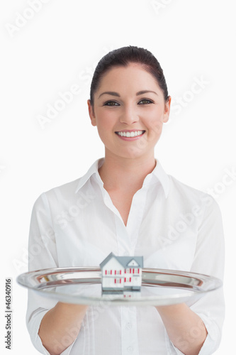 Smiling waitress holding tray with miniature house