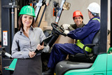 Confident Female Supervisor With Forklift Driver At Warehouse poster