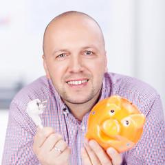 lächelnder mann mit sparschwein und stromstecker