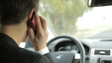 Handsome man driving car and talking on the phone